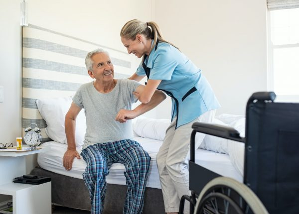 Nurse helping old patient get up