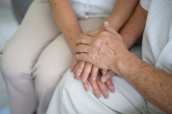 Old people holding hands each other